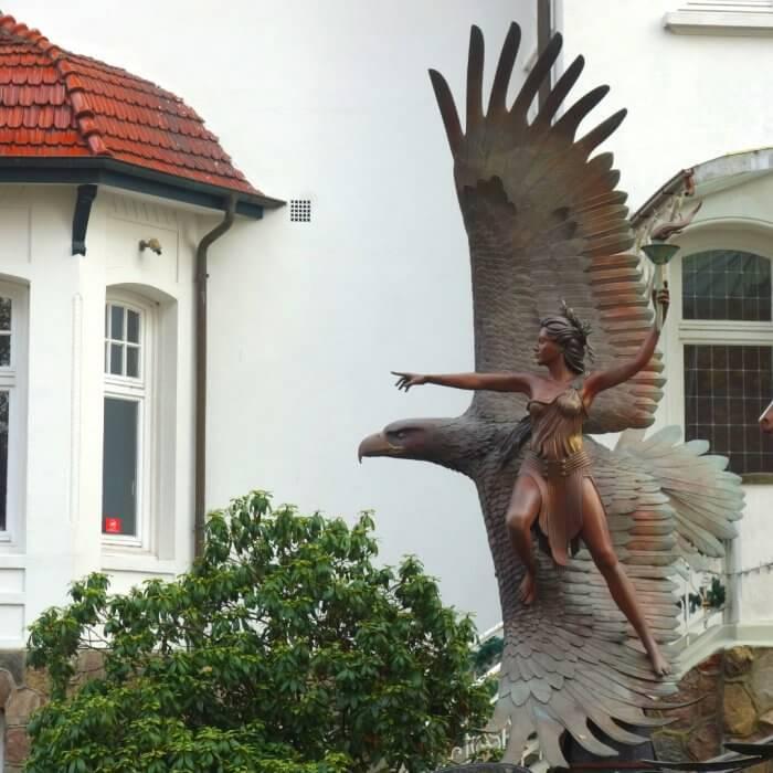 Eine Amazone aus Bronze steht auf den dem Flügel eines Adlers, Statue von Osprey Orielle Lake